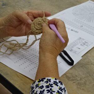 編み図に従って編み込んでいく受講者